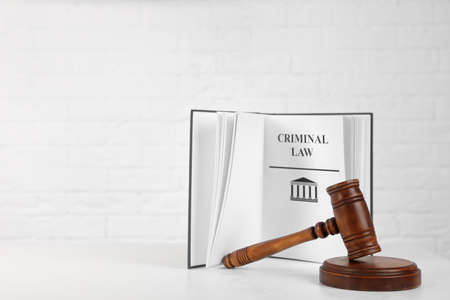 Book with words CRIMINAL LAW and gavel on table against white background. Space for text Zdjęcie Seryjne