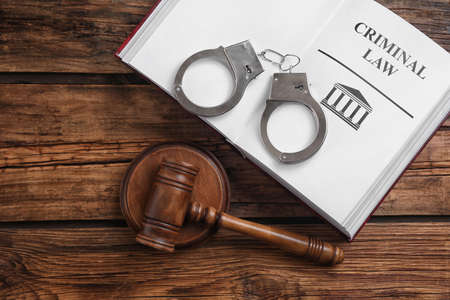 Book with words CRIMINAL LAW, handcuffs and gavel on wooden table, flat lay Zdjęcie Seryjne