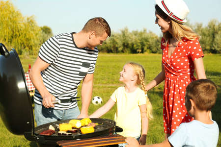 Happy family with little children having barbecue in park Imagens