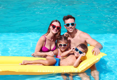 Happy family with inflatable mattress in swimming pool Imagens