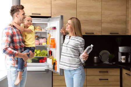 Happy family with bottle of water near refrigerator in kitchen Imagens