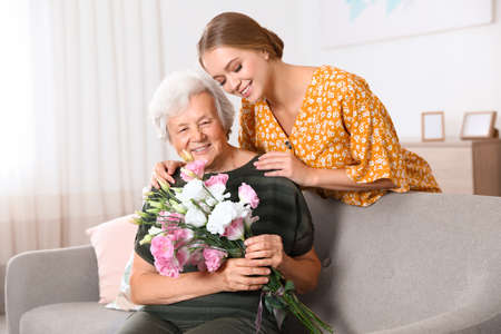 Young woman congratulating her senior mom at home. Happy Mother's Day