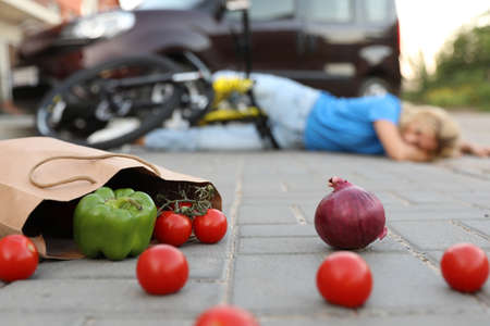 Woman fallen from bicycle after car accident outdoors, focus on scattered vegetables