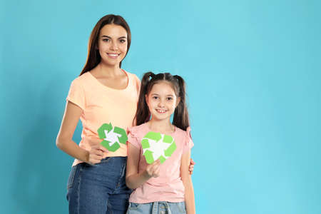 Mother and daughter with recycling symbols on blue background. Space for text Imagens