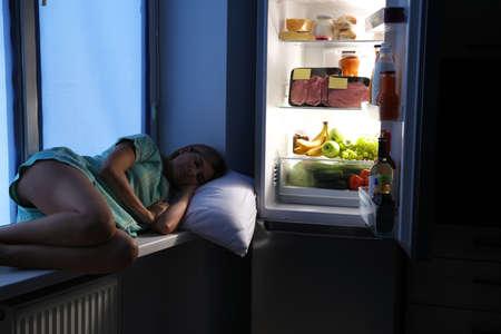 Woman sleeping on window sill near open refrigerator in kitchen at night Zdjęcie Seryjne