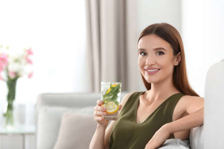 Young woman with lemonade at home. Refreshing drink Imagens
