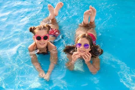 Happy cute girls in swimming pool on sunny day