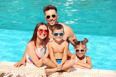 Happy family in swimming pool on sunny day Imagens