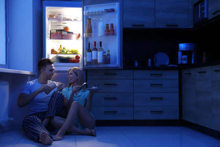 Happy couple eating near refrigerator in kitchen at night Banco de Imagens
