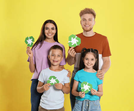 Young family with recycling symbols on yellow background Reklamní fotografie - 132241523