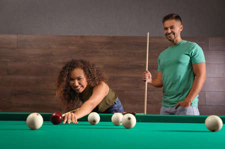 Young man and woman playing billiard indoors