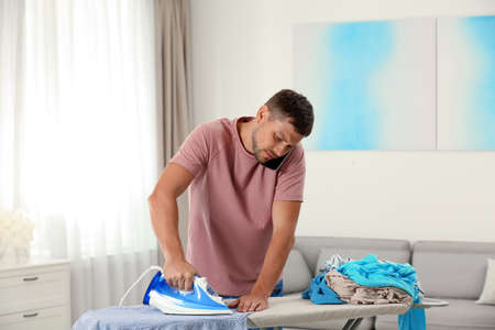 Handsome man ironing clean laundry while talking smartphone at home