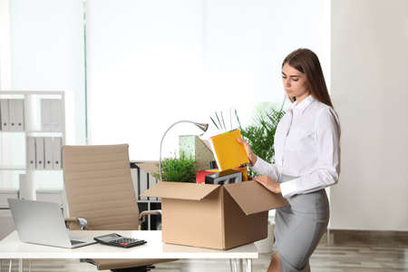 Upset young woman packing stuff in box at office Standard-Bild - 132003314