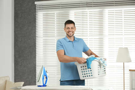 Handsome man with iron and clean laundry near board at home Foto de archivo - 132038545