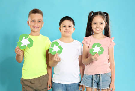 Children with recycling symbols on blue background