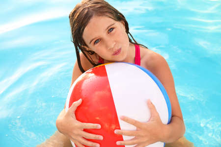 Happy cute girl with inflatable ball in swimming pool Foto de archivo