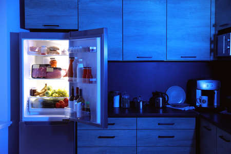 Open refrigerator full of products in kitchen at night