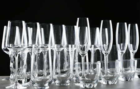 Set of empty glasses on table against black background