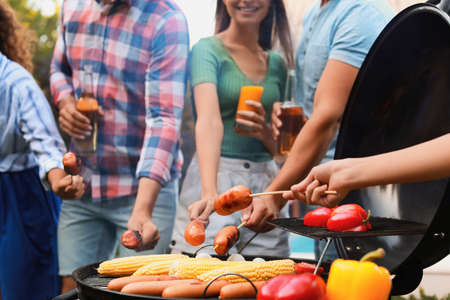 Group of friends with grilled sausages at barbecue party outdoors