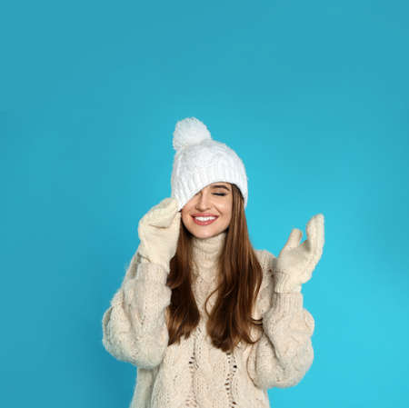Beautiful young woman in warm clothes on blue background. Winter season