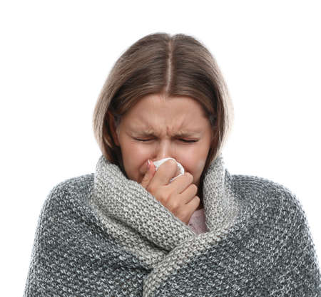 Young woman wrapped in warm blanket suffering from cold on white background