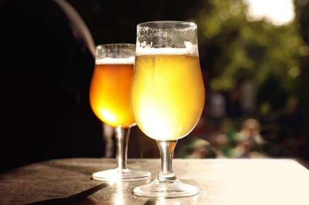 Gläser kaltes leckeres Bier auf Holztisch im Freien Standard-Bild