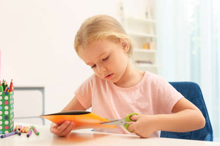 Little left-handed girl cutting construction paper at table