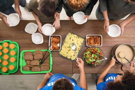Volunteers serving food to poor people indoors, top view