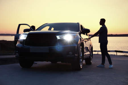 Young man standing near family car at sunset