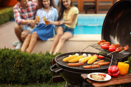Barbecue grill with fresh food and blurred people on background