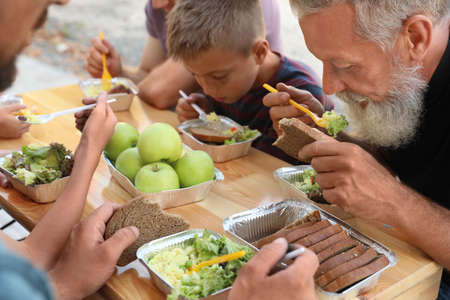 Poor people eating food at wooden table outdoors