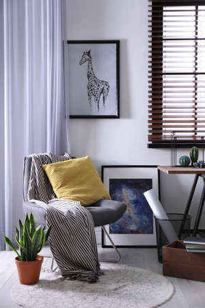 Comfortable armchair and table near window with horizontal blinds Stock Photo