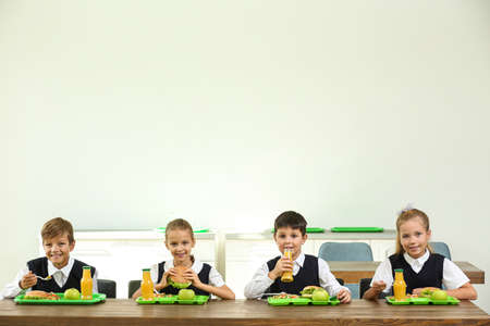 Happy children eating healthy food for lunch in school canteen Imagens
