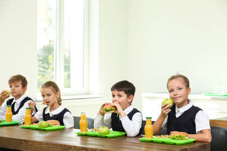 Happy children eating healthy food for lunch in school canteen Reklamní fotografie