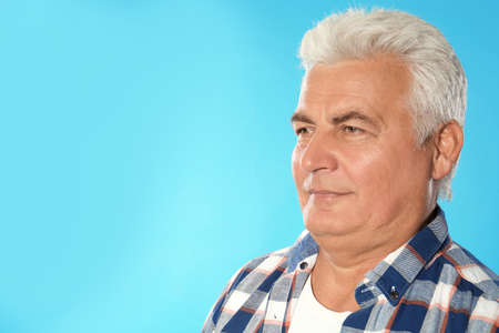 Mature man with double chin on blue background. Space for text