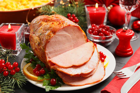 Delicious Christmas ham served with garnish on dark table