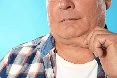 Mature man with double chin on blue background, closeup Stock Photo