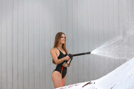 Young woman in swimsuit with high pressure water jet cleaning automobile at car wash Stok Fotoğraf