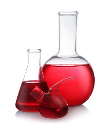 Set of laboratory glassware with red liquid on white background