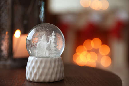 Snow globe on wooden table against blurred background, space for text. Bokeh effect