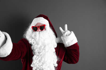 Authentic Santa Claus taking selfie on grey background