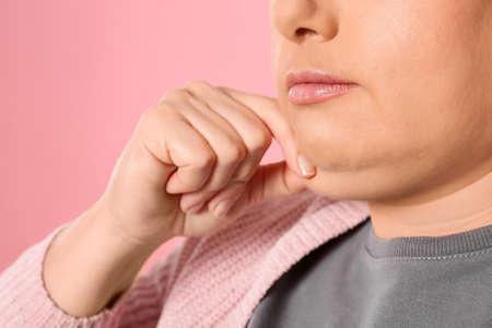 Mujer con papada sobre fondo rosa, primer plano