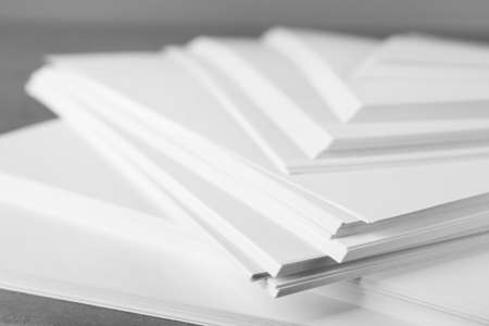 Stack of blank paper on grey table, closeup