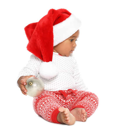 Festively dressed African-American baby with Christmas ball on white background