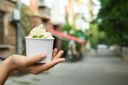 Woman holding cup with tasty frozen yogurt outdoors, closeup. Space for text Banque d'images - 131559873