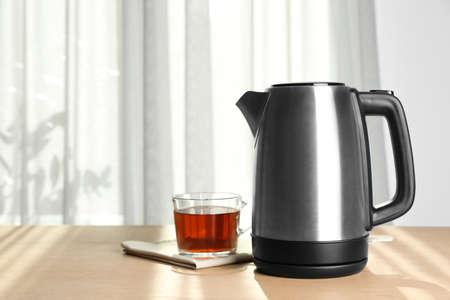 Bollitore elettrico moderno e tazza di tè sulla tavola di legno all'interno. Spazio per il testo