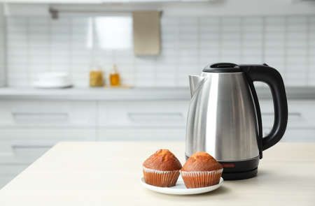 Modern electric kettle and muffins on wooden table in kitchen. Space for text