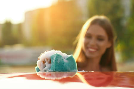 Young woman washing car outdoors, focus on sponge