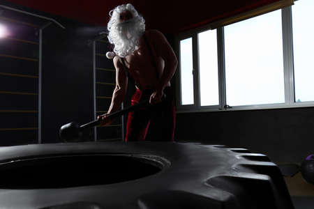 Young Santa Claus hitting heavy tire with hammer in modern gym