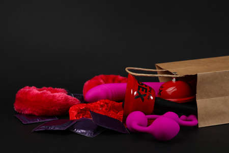 Shopping bag and different sex toys on black background